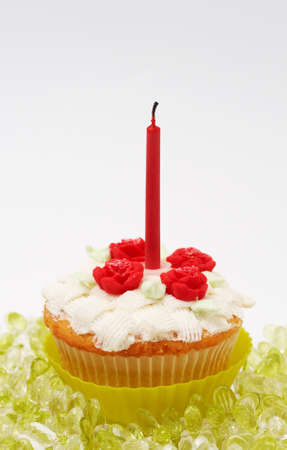 buttercream: Fresh vanilla cupcake with basketweave buttercream icing and roses and birthday candle on white background
