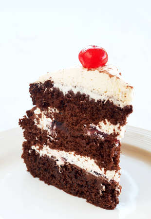 chocolate slice: Slice of Black Forest cake with fresh cream and cherries, served on a white plate  Stock Photo