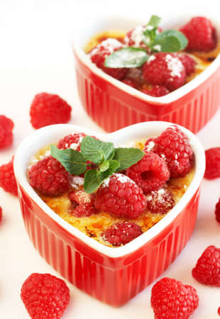 French creme brulee dessert with raspberries and mint covered with caramelized sugar in red heart shaped ramekins on white background Stock Photo