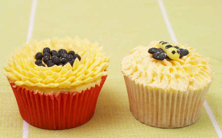 Fresh vanilla cupcakes with sunflower buttercream icing and bee decorations on green background photo