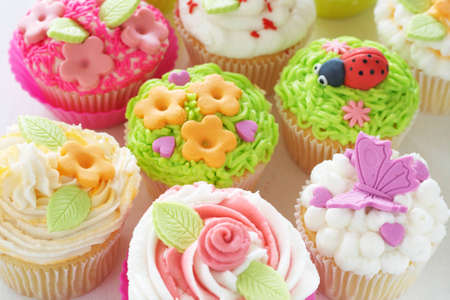 patisserie: Vanilla cupcakes with buttercream icing and various decorations