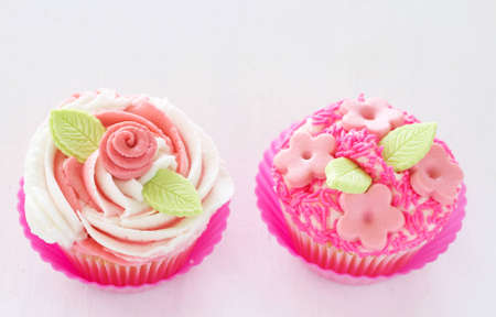 buttercream: Vanilla cupcakes with buttercream icing and pink flower decorations on white background