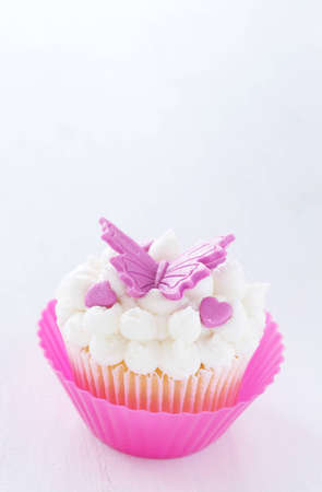 vanilla cupcake: Vanilla cupcake with buttercream icing and butterfly decorations on white background
