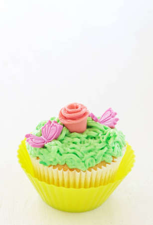 buttercream: Vanilla cupcakes with buttercream icing and rose decorations on white background