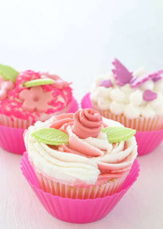 buttercream: Vanilla cupcakes with buttercream icing and various decorations on white background