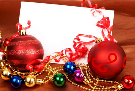 Red and other colorful Christmas baubles and white card with copy space.  photo