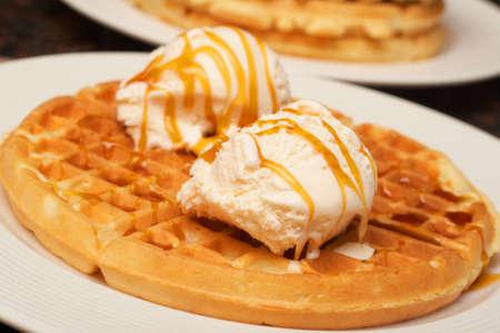 waffles: Gofres belgas con helado y jarabe en un plato blanco