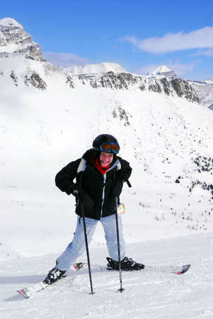 Young girl downhill skiing on the backdrop of scenic view in Canadian Rocky mountains ski resort
