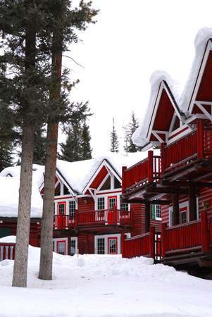 log cabin winter: Log buildings of a mountain lodge in winter at ski resort Stock Photo