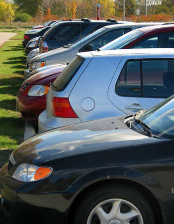 Row of cars in the parking lot on a bright fall day; no logostrademarks are visible Imagens