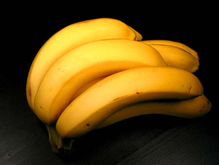 Bunch of yellow bananas on black background