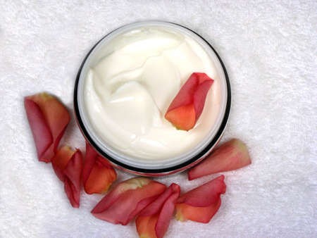 Body cream with rose petals on white towel Stock Photo