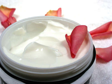 Body cream with rose petals on white towel, closeup Stock Photo