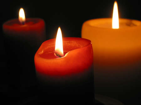 Three candles burning in the dark, focus on the front candle photo