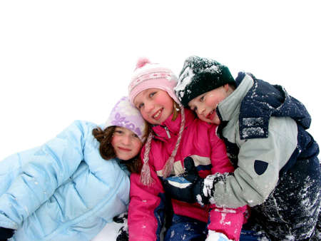 Three children having fun in the fresh white snow photo