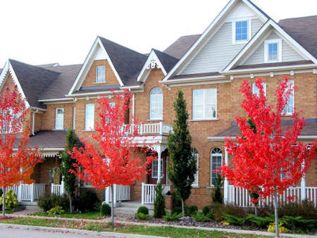 townhomes: A row of new modern townhomes with bright red autumn trees Stock Photo
