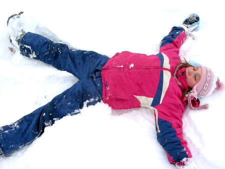 Winter fun: young girl making a snow angel on fresh white snow Stock Photo - 351599
