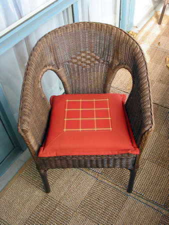 Brown wicker chair with red cushion
