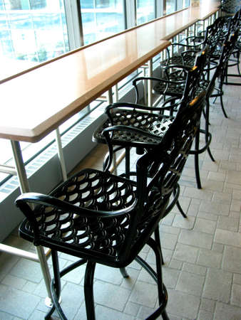 prespective: Wrought iron bar stools at the counter in an empty cafe Stock Photo