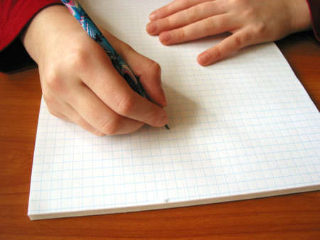 Closeup on the hands of a child starting to white on the new blank page, space for copy Stock Photo