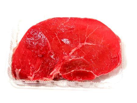 steak cru: Raw steak dans un contenant de plastique sur fond blanc  Banque d'images