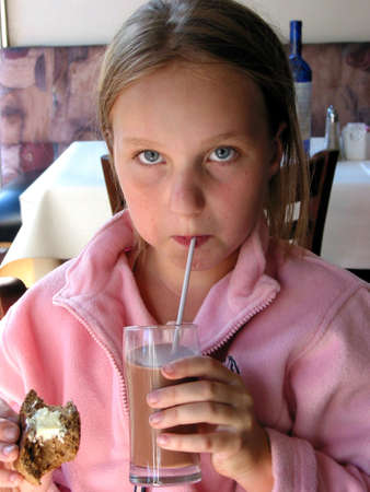 Young girl in a restaurant drinking chocolate milk Stock Photo
