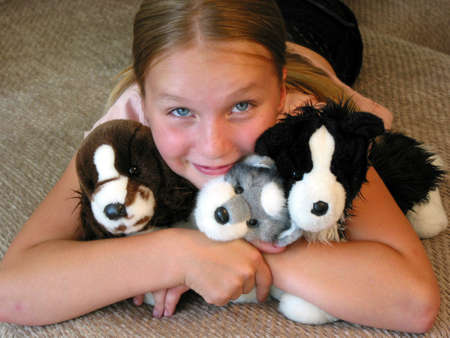 favourite: Happy young girl with her favourite plush toys. Stock Photo