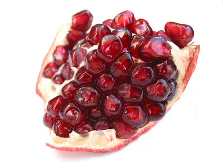A piece of open pomegranate with seeds isolated on white background photo