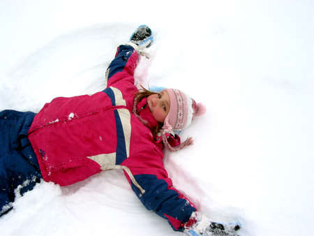 Young girl making a snow angel on fresh white snow Stock Photo - 352486