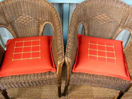 2 brown wicker patio chairs with red cushions