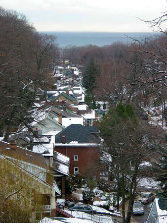 View of a winter street with snow covered roofs from above, sea in the background photo