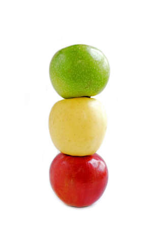 Three apples on white background on top of each other: green, yellow and red