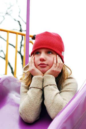 hesitating: Ni�a en un sombrero rojo en campo de juegos, el pensamiento