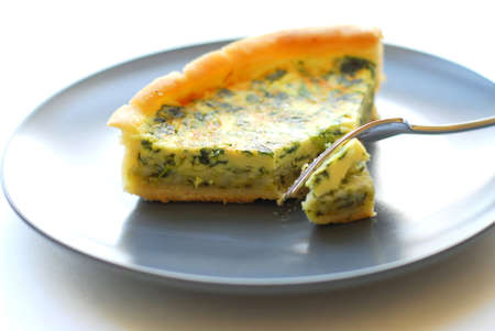 Spinach quiche on a plate with fork photo