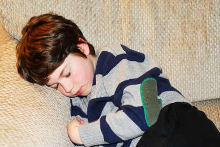 Cute boy sleeping on a couch Imagens