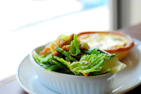 Caesar salad and quiche on white plate photo