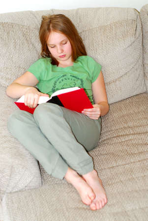 Young girl reading a book on a couch