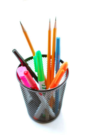 Pens and pencils in metal mesh pencil holder on white background photo