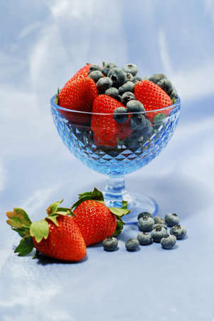 Strawberries and blueberries in blue glass bowl on blue background