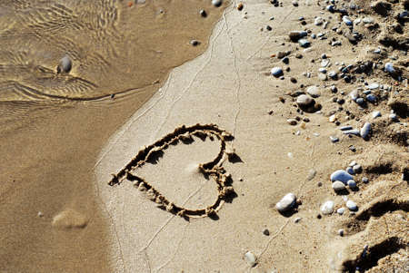 Heart drawn on a sandy beach, about to be washed away by a wave