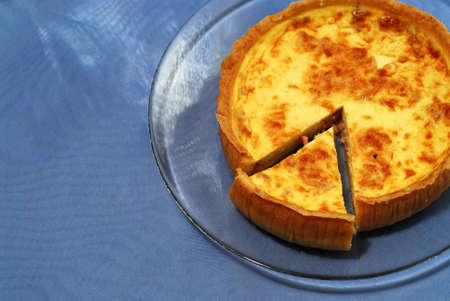 Whole quiche on a clear plate with slice cut out, blue background photo