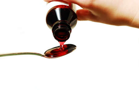 cold remedy: Cough syrup poured into a spoon Stock Photo