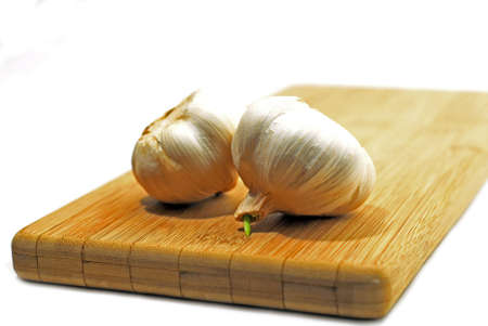 Two garlic bulbs on wooden cutting board, white background photo