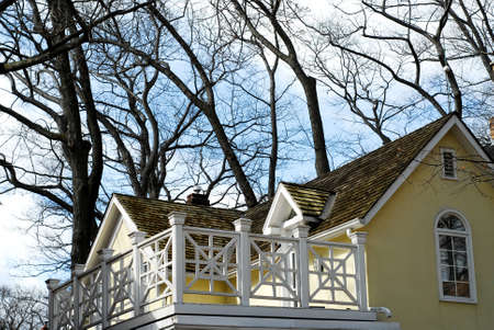 yellow house: Yellow house with white balcony surrounded by oak trees Stock Photo