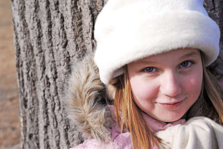 Portrait of a young girl in winter hat smiling