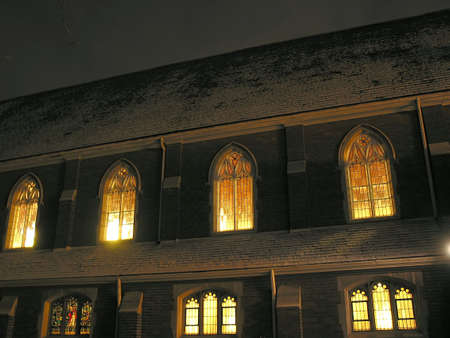 Beautiful old church in Toronto at night with brightly lit windows and snow covered roof photo