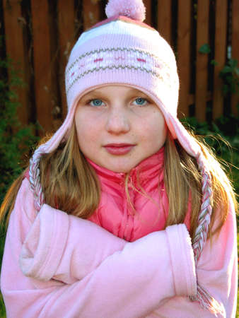 shiver: Young girl shivering in cold weather, wearing winter hat