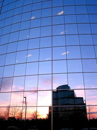 edificio corporativo: Reflejo de una puesta de sol en el espejo de una pared de vidrio edificio corporativo