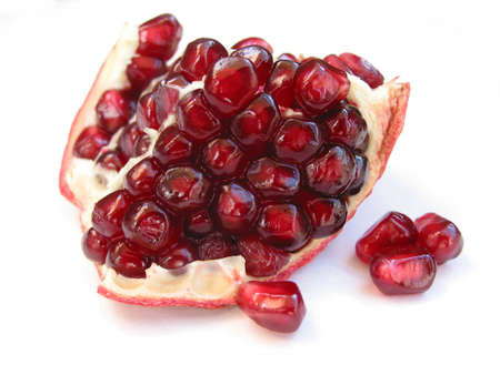 A piece of pomegranate with seeds closeup on white backgound
