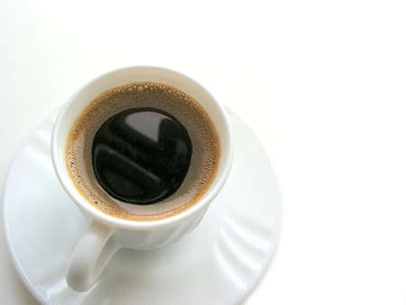 foamy: Foamy espresso coffee in a white cup with saucer on white background, top view, space for copy